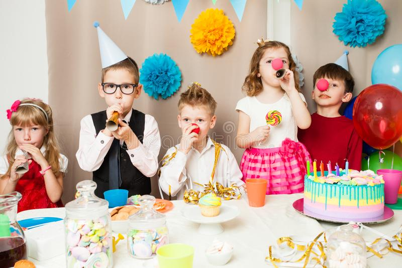 Funny birthday games. Group of smiling children playing on the birthday party in decorated room. Happy kids blowing in pipes on birthday party stock image