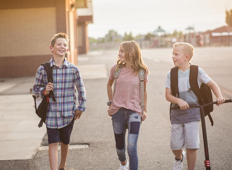 Group of smiling elementary school students on their way home royalty free stock photo