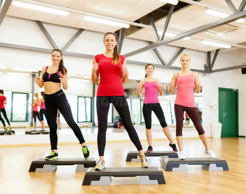 Group of smiling female doing aerobics. Fitness, sport, training, gym and lifestyle concept - group of smiling female doing aerobics stock photography