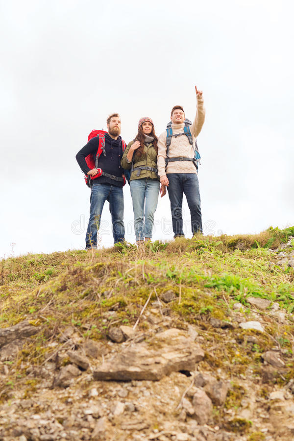 Group of smiling friends with backpacks hiking. Adventure, travel, tourism, hike and people concept - group of smiling friends with backpacks pointing finger royalty free stock photos