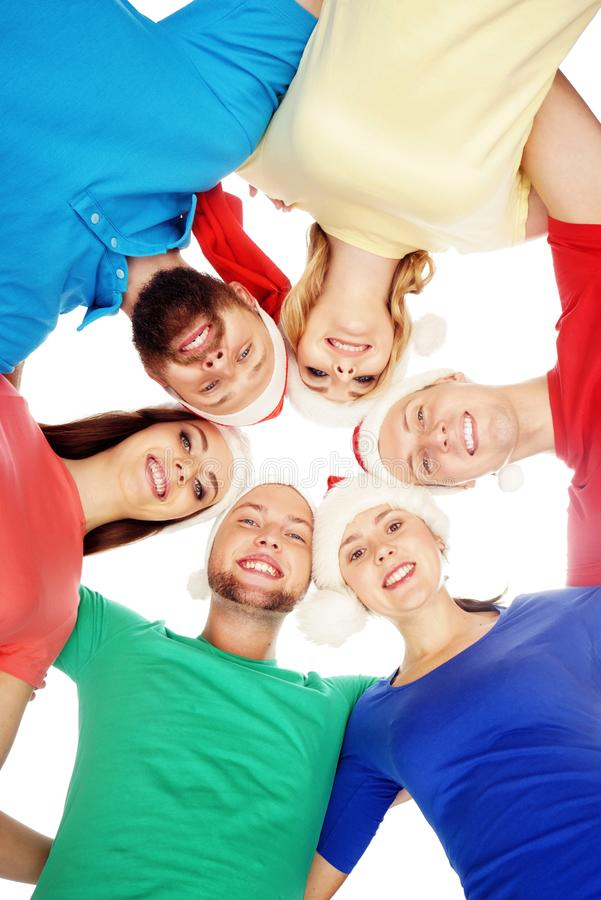 Group of smiling friends in Christmas hats embracing together. stock images