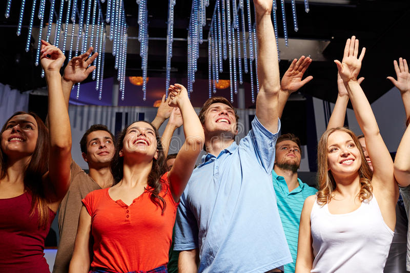 Group of smiling friends at concert in club. Party, holidays, celebration, nightlife and people concept - group of smiling friends waving hands at concert in royalty free stock photo