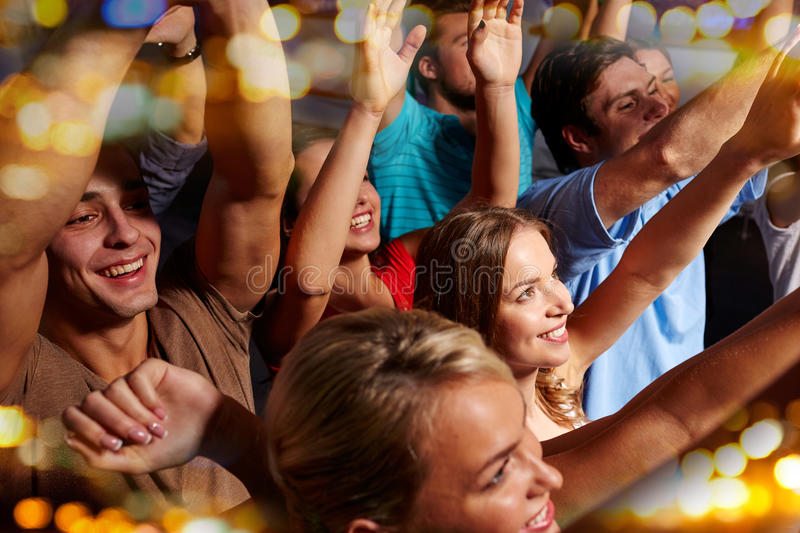 Group of smiling friends at concert in club. Party, holidays, celebration, nightlife and people concept - group of smiling friends waving hands at concert in stock photography