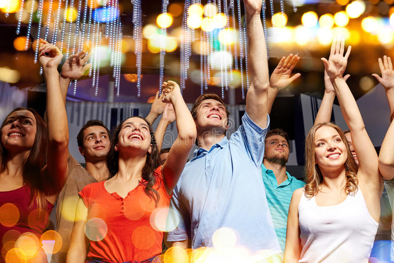 Group of smiling friends at concert in club. Party, holidays, celebration, nightlife and people concept - group of smiling friends waving hands at concert in royalty free stock images