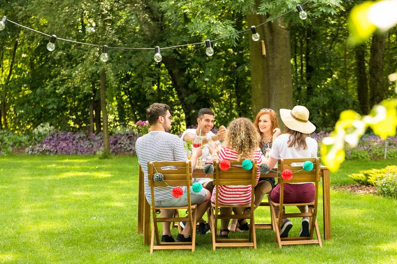 Group of smiling friends enjoying outdoor birthday party during stock images