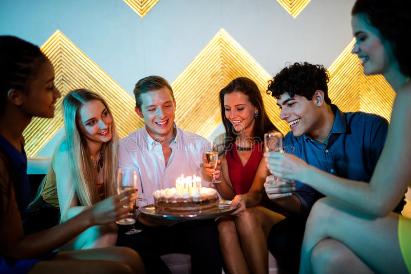 Group of smiling friends having a glass of champagne while celebrating birthday. At bar royalty free stock photos