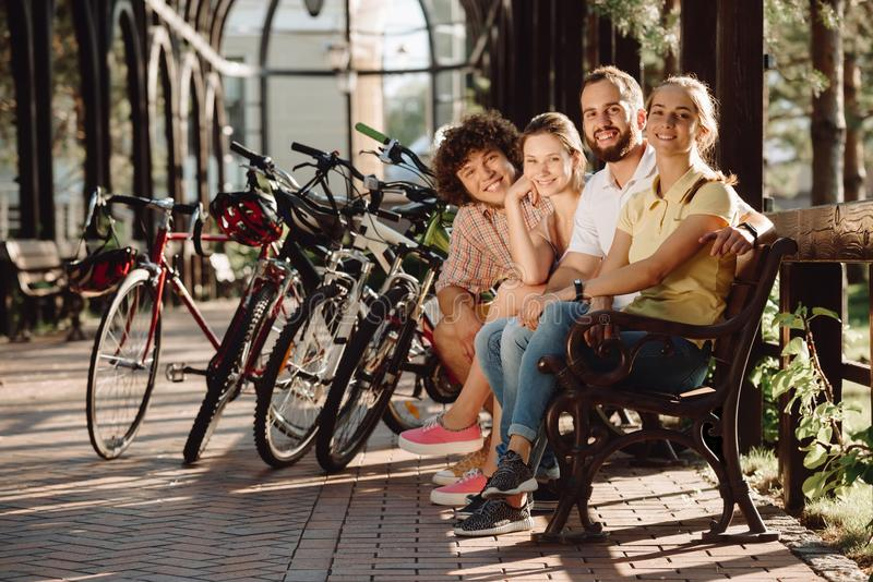 Group of smiling friends looking at camera. Young cheerful friends sitting on bench outdoors. People and summer rest royalty free stock photography