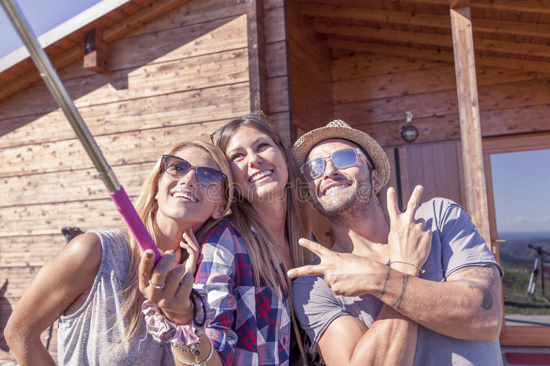 Group of smiling friends taking funny selfie with smart phone stock photo