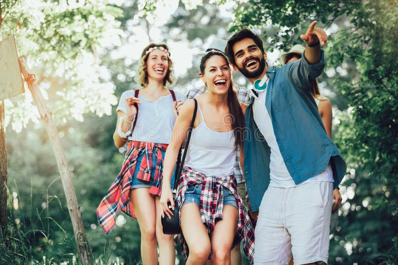 Smiling friends walking with backpacks in woods - adventure, travel, tourism, hike and people concept stock image