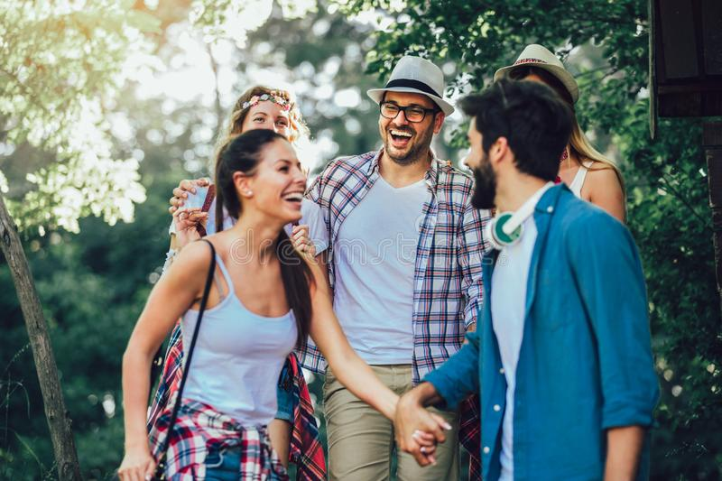 Smiling friends walking with backpacks in woods - adventure, travel, tourism, hike and people concept stock photos