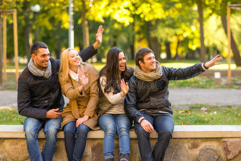 Group of smiling friends waving hands in city park royalty free stock photo