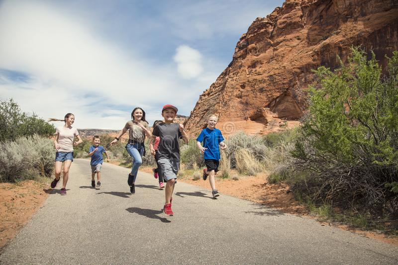 Group of smiling kids running together outdoors. A large group of smiling kids running together on a pathway at a national park. Having fun out in nature during stock image