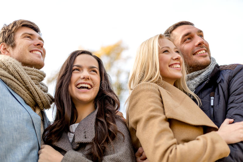 Group of smiling men and women in autumn park. Love, relationship, season, friendship and people concept - group of smiling men and women hugging in autumn park royalty free stock image