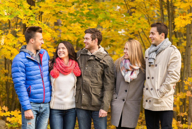 Group of smiling men and women in autumn park. Love, relationship, season, friendship and people concept - group of smiling men and women hugging in autumn park stock photos