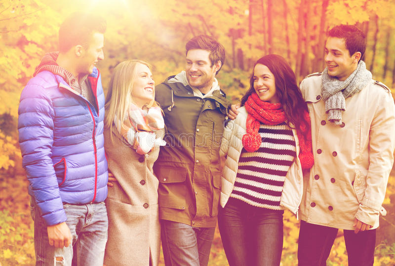 Group of smiling men and women in autumn park. Love, relationship, season, friendship and people concept - group of smiling men and women hugging in autumn park royalty free stock photography