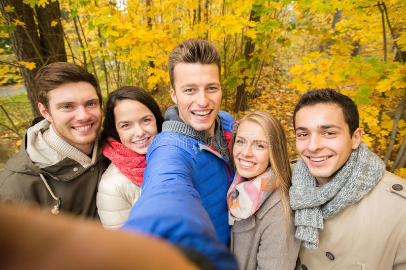 Group of smiling men and women in autumn park. Technology, season, friendship and people concept - group of smiling men and women taking selfie with smartphone royalty free stock photos