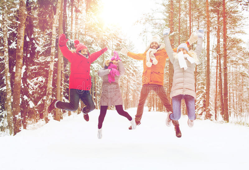 Group of smiling men and women in winter forest. Leisure, season, friendship and people concept - group of smiling men and women having fun and jumping in winter stock images