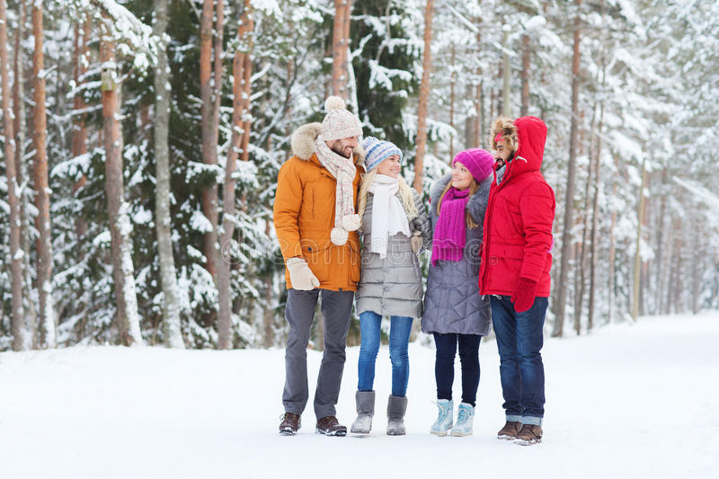 Group of smiling men and women in winter forest. Love, relationship, season, friendship and people concept - group of smiling men and women talking in winter stock image