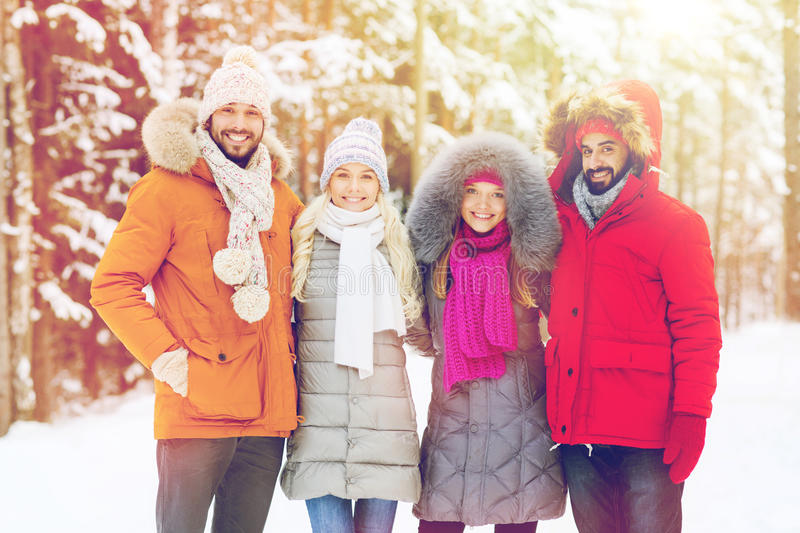Group of smiling men and women in winter forest. Love, relationship, season, friendship and people concept - group of smiling men and women walking in winter royalty free stock image