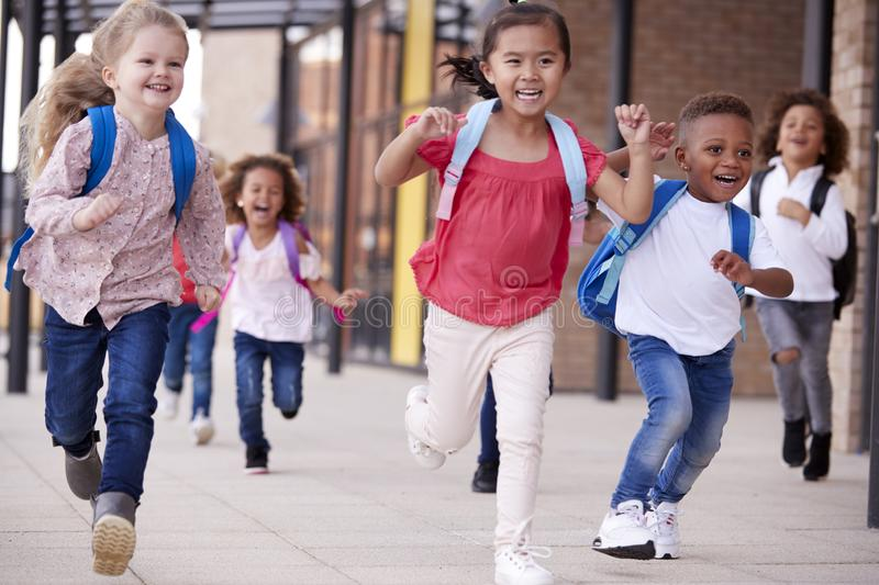 A group of smiling multi-ethnic school kids running in a walkway outside their infant school building after a lesson, close up stock photography