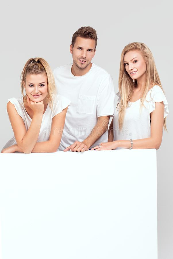 Group of smiling people with empty white board. stock images