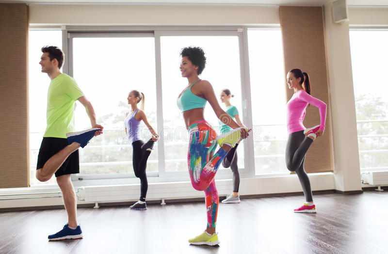 Group of smiling people exercising in gym royalty free stock photos