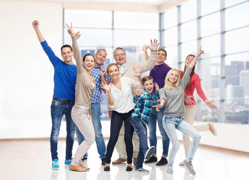 Group of smiling people having fun. Family, gender, generation and people concept - group of happy men, women and boy having fun and waving hands over empty royalty free stock photos