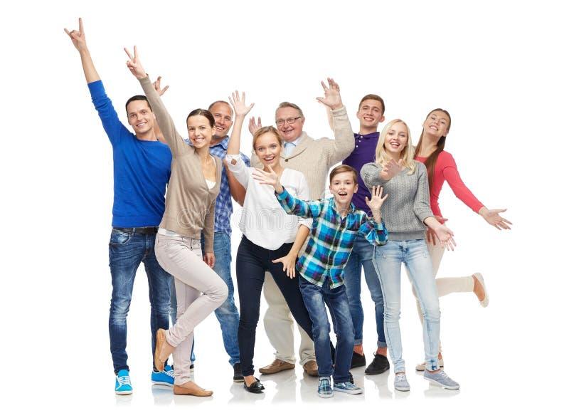 Group of smiling people having fun. Family, gender, generation and people concept - group of smiling men, women and boy having fun and waving hands royalty free stock image