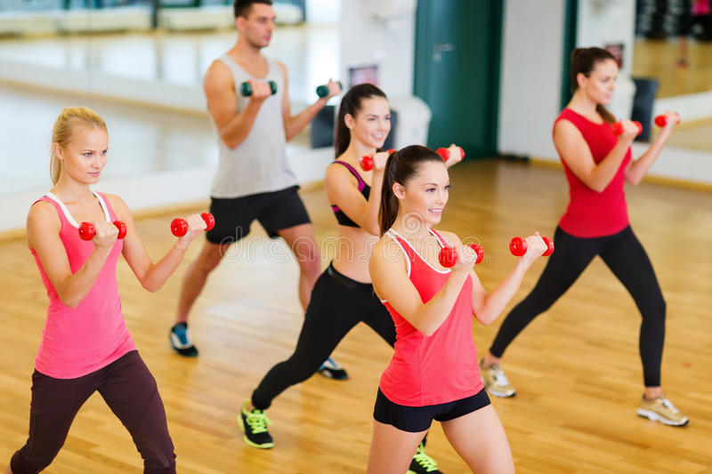 Group of smiling people working out with dumbbells stock image