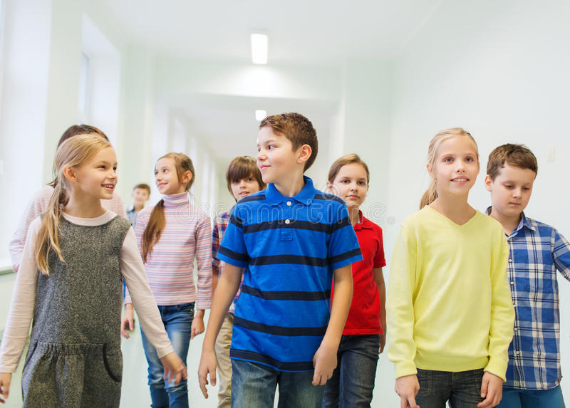 Group of smiling school kids walking in corridor. Education, elementary school, drinks, children and people concept - group of smiling school kids walking in stock photography