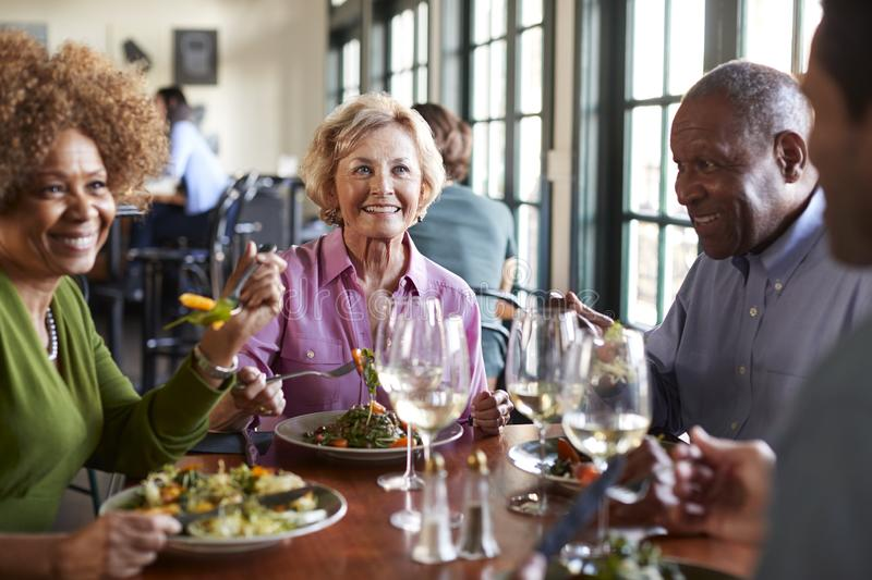 Group Of Smiling Senior Friends Meeting For Meal In Restaurant stock photography
