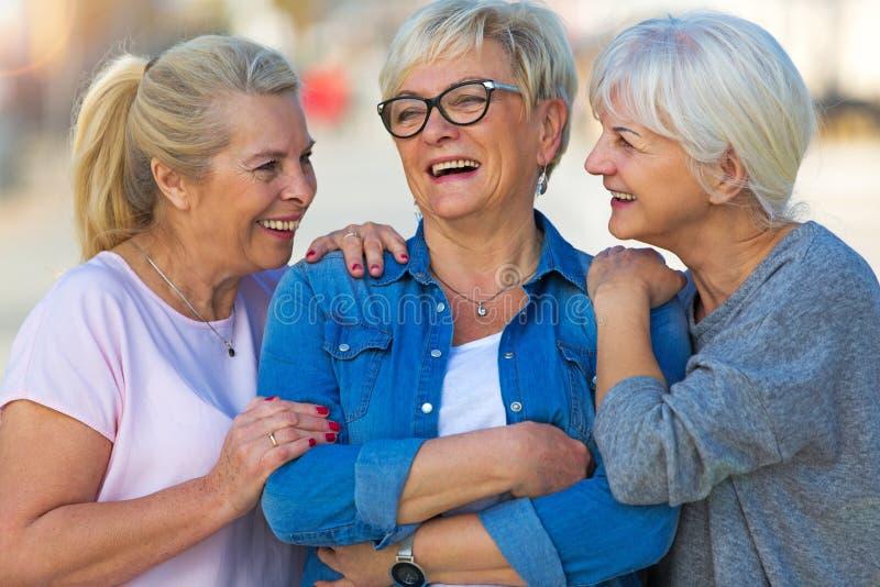 Group of senior women smiling. Group of smiling senior women standing outside stock photo