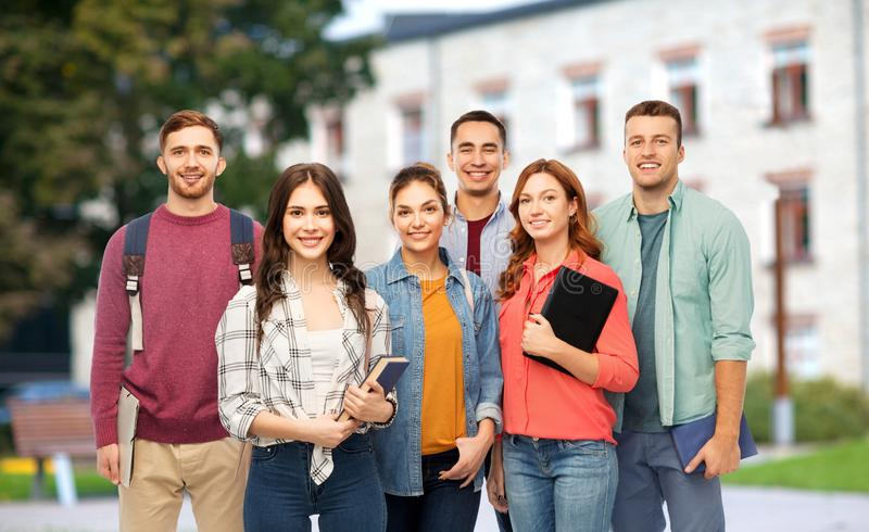 Group of smiling students with books over campus. Education, high school and people concept - group of smiling students with books over campus background stock photography