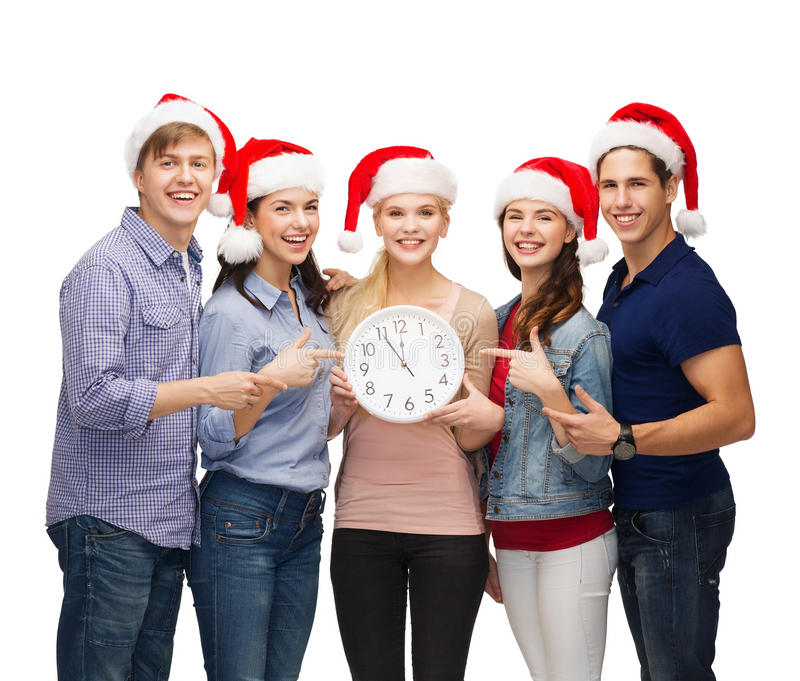 Group of smiling students with clock showing 12 royalty free stock photo