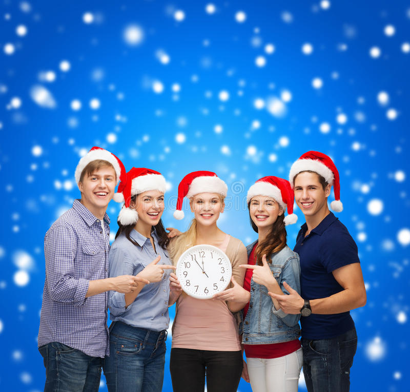 Group of smiling students with clock showing 12 royalty free stock image