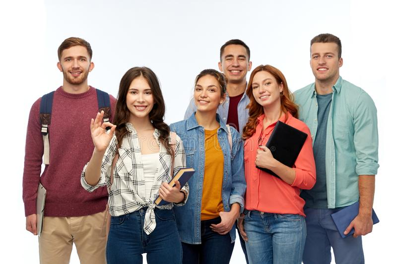 Group of smiling students showing ok hand sign stock photography