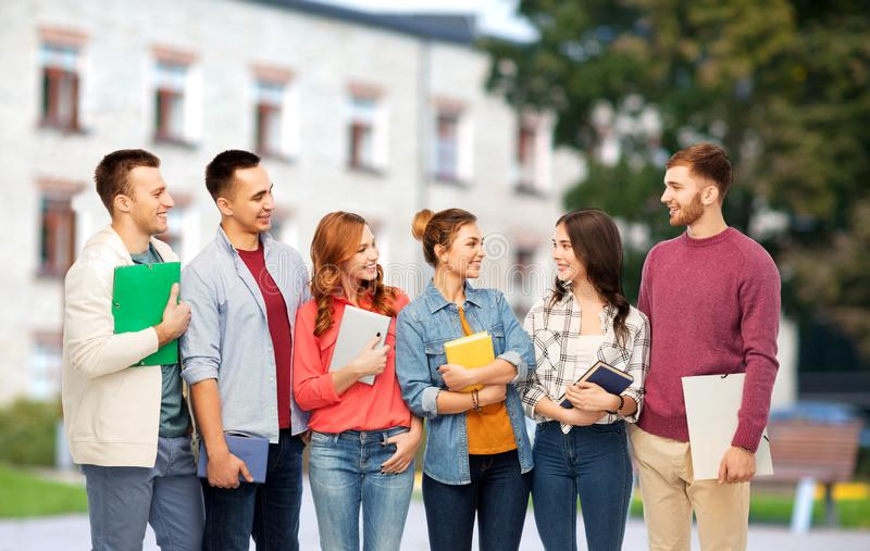 Group of smiling students talking over campus. Education, high school and people concept - group of smiling students talking over campus background royalty free stock photography