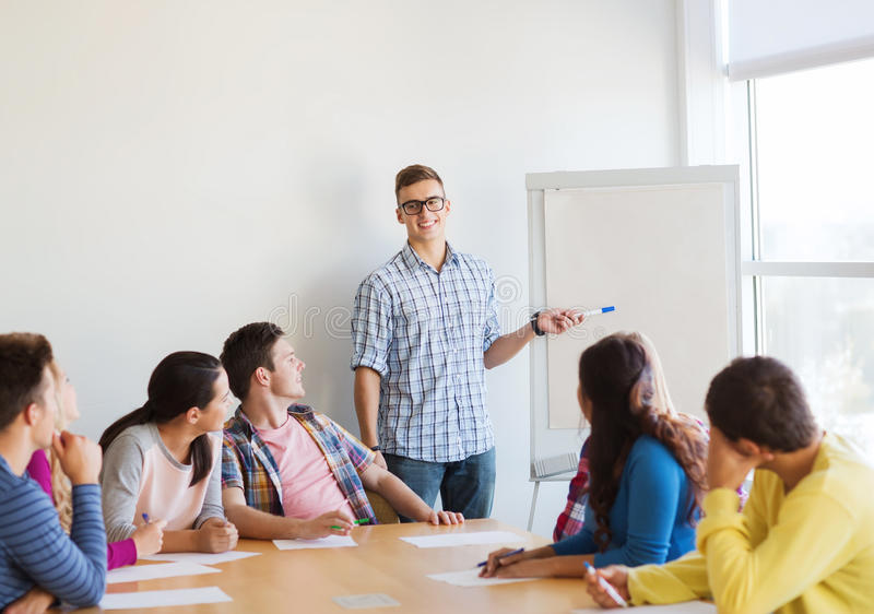 Group of smiling students with white board stock photo