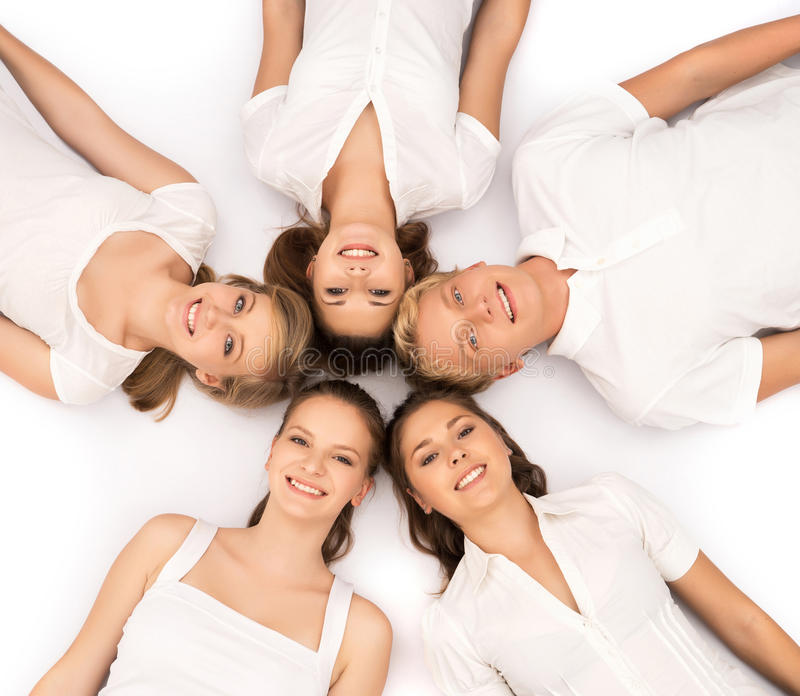 Group of smiling teenage friends looking at camera. Isolated on white stock images