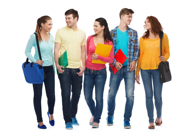 Group of smiling teenagers with folders and bags. Friendship, youth, education and people - group of smiling teenagers with folders and bags royalty free stock photos