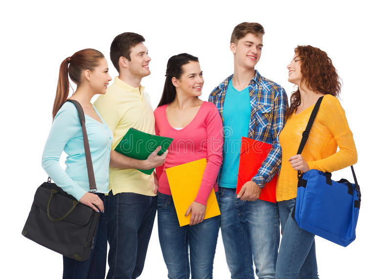 Group of smiling teenagers. Friendship, youth, education and people concept - group of smiling teenagers with folders and school bags stock images