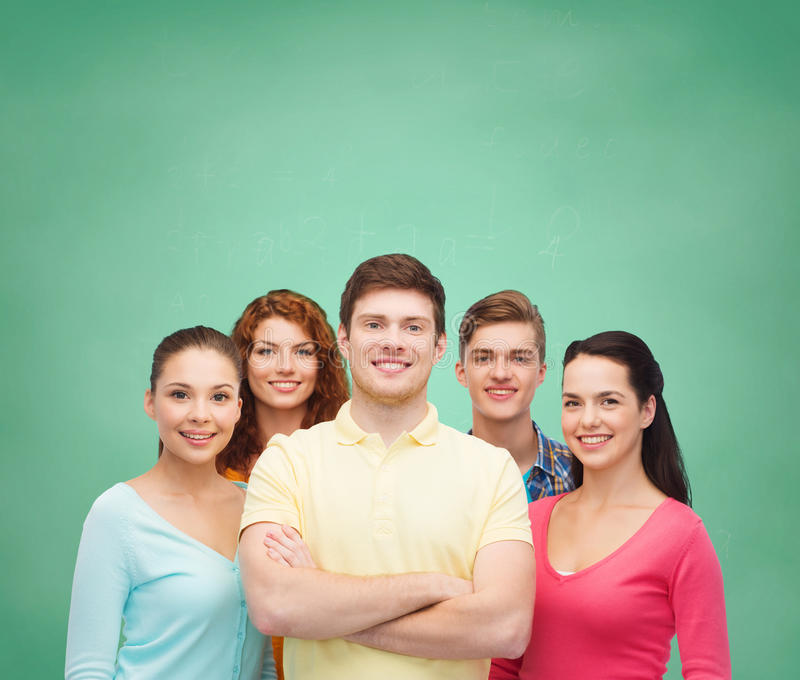 Group of smiling teenagers over green board stock photos