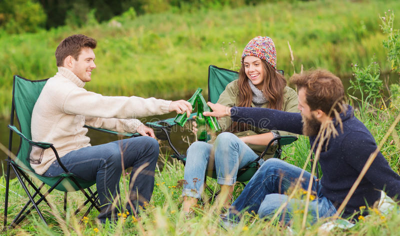 Group of smiling tourists drinking beer in camping. Adventure, travel, tourism, friendship and people concept - group of smiling tourists clinking beer bottles stock images