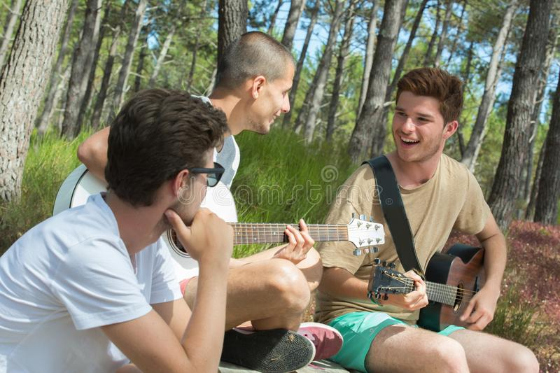 Group smiling tourists playing guitar. Group of smiling tourists playing guitar stock photography