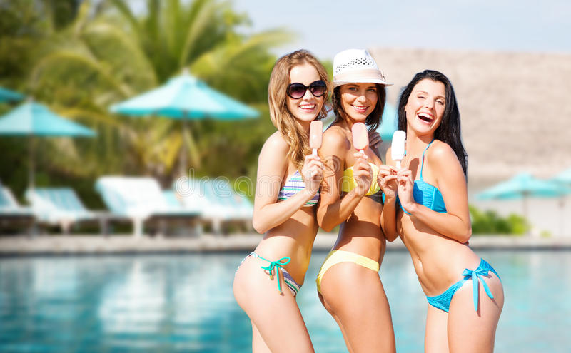 Group of smiling women eating ice cream on beach royalty free stock images