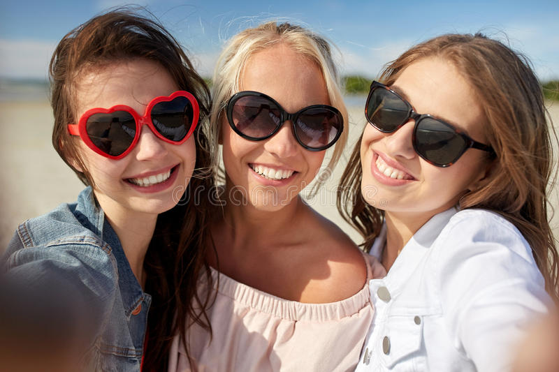 Group of smiling women taking selfie on beach. Summer vacation, holidays, travel and people concept- group of smiling young women taking selfie on beach royalty free stock photography