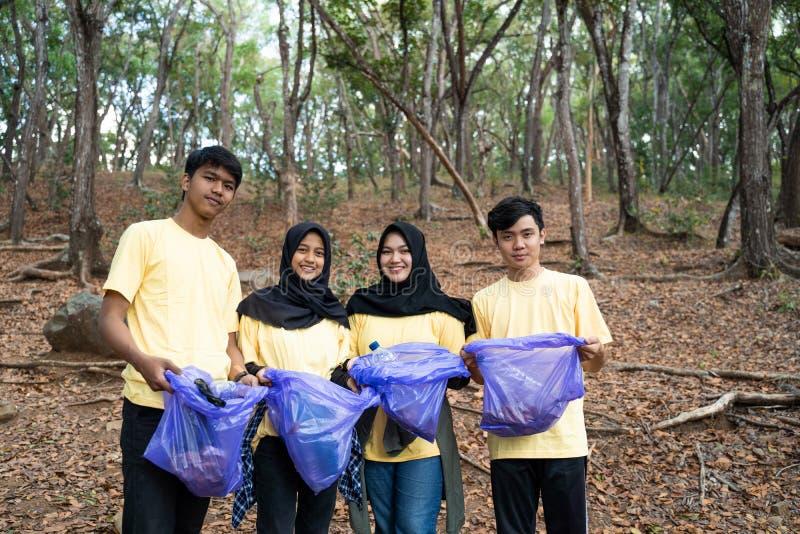 Group of smilling volunteer holding trash bag stock image