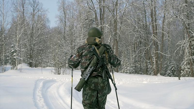 Group of soldiers run on skis in the woods with weapons. Clip. Soldiers with AK-47 rifles and grenade launchers running stock photography