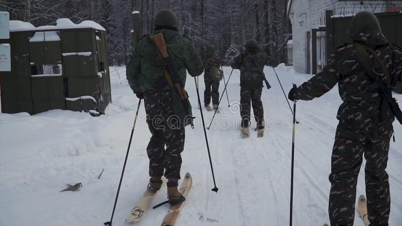 Group of soldiers run on skis in the woods with weapons. Clip. Soldiers with AK-47 rifles and grenade launchers running stock photo
