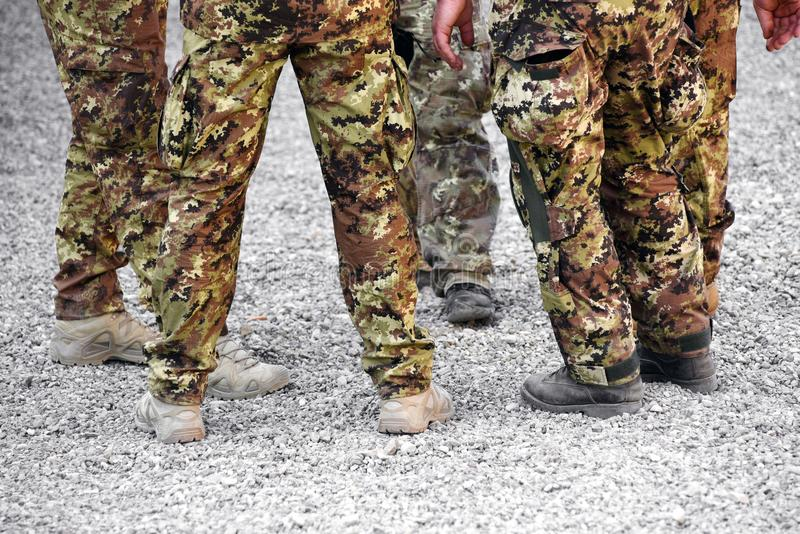 Group of soldiers wearing camouflage fatigues. In a low angle view of their legs on gravel stock images